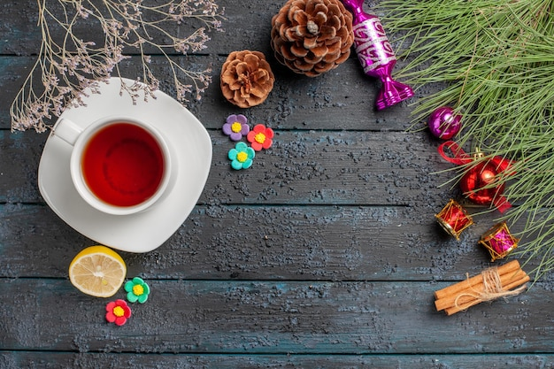 Vue de dessus une tasse de thé une tasse de thé noir sur la soucoupe blanche à côté des bâtons de cannelle citron branches d'épinette avec des jouets de noël et des cônes sur la table