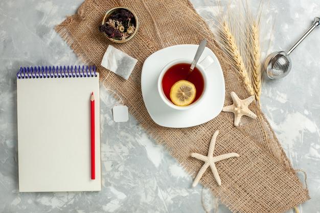 Vue de dessus tasse de thé avec une tranche de citron sur un mur blanc boire du thé aux fruits citron