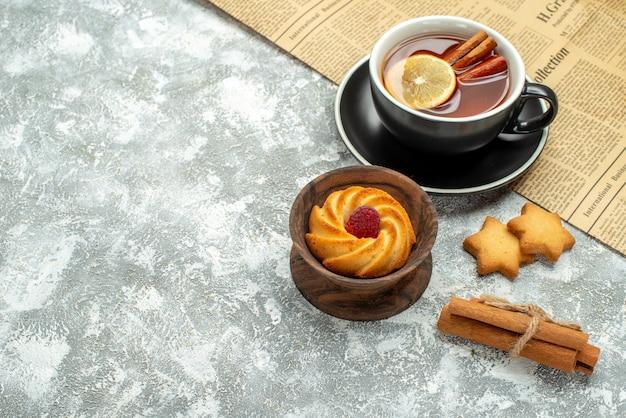 Vue de dessus une tasse de thé avec des tranches de citron et des bâtons de cannelle sur les biscuits de journaux sur le lieu de copie de surface grise