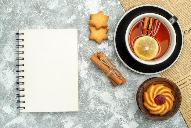 Vue de dessus une tasse de thé avec des tranches de citron et des bâtons de cannelle sur les cookies de cahier de journal sur la surface grise