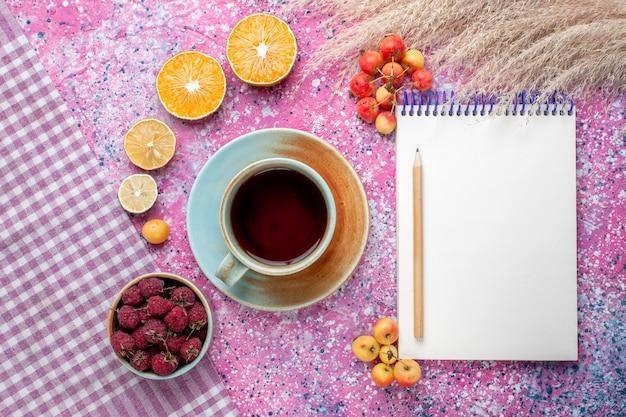 Vue de dessus de la tasse de thé avec des tranches d'orange et des framboises sur la surface rose