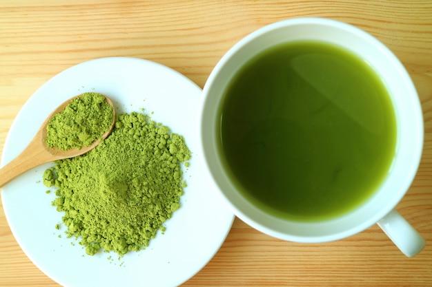 Vue de dessus d'une tasse de thé vert matcha chaud avec une assiette de poudre de thé matcha sur une table en bois
