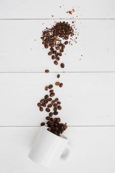 Vue de dessus de la tasse tombée avec des grains de café