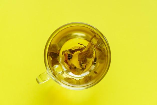 Vue de dessus d'une tasse transparente avec du thé vert sur fond jaune.