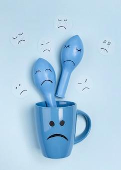 Vue de dessus de la tasse triste avec des ballons avec des froncements de sourcils pour le lundi bleu
