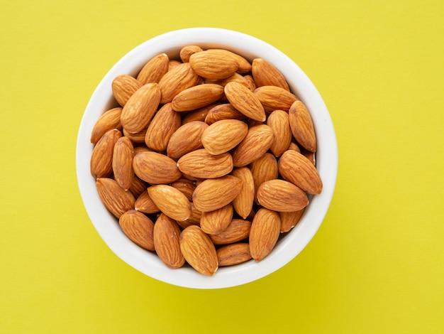 Vue de dessus de tasses blanches, bols avec une poignée de noix de pécan, amandes sur une couleur de fond jaune vif
