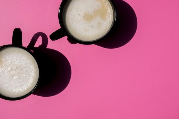 Vue de dessus des tasses de café sur fond rose