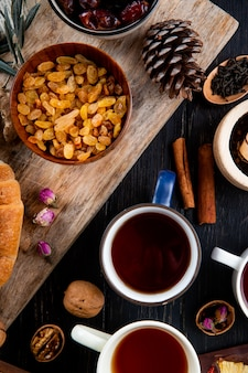 Vue de dessus des tasses de thé avec des raisins secs dans un bol sur rustique