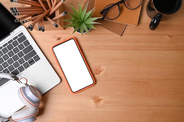 Vue de dessus téléphone portable, ordinateur portable, porte-crayon, tasse à café et casque sur fond en bois.