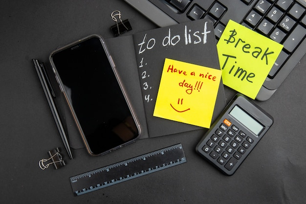 Vue de dessus temps de pause et bonne journée écrite sur des notes autocollantes à faire liste sur bloc-notes noir téléphone stylo calculatrice règle reliure clips clavier sur tableau noir