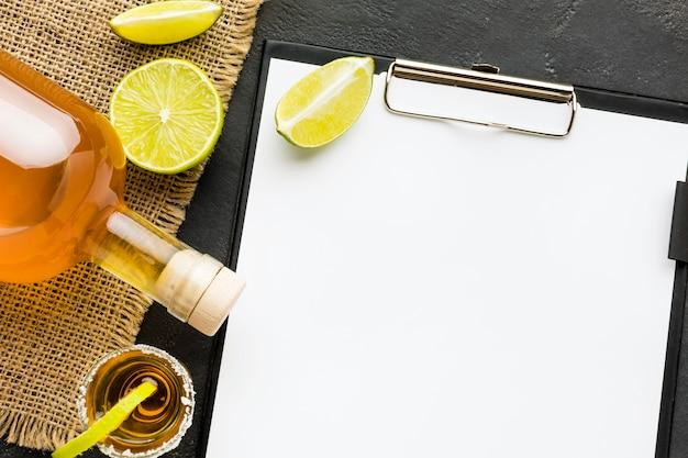 Vue de dessus de la tequila shot et tranches de citron vert avec bouteille et presse-papiers vierge
