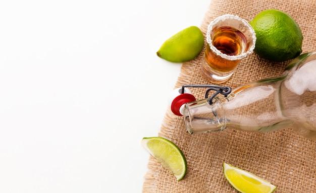 Vue de dessus de la tequila shot et tranches de citron vert avec copie espace