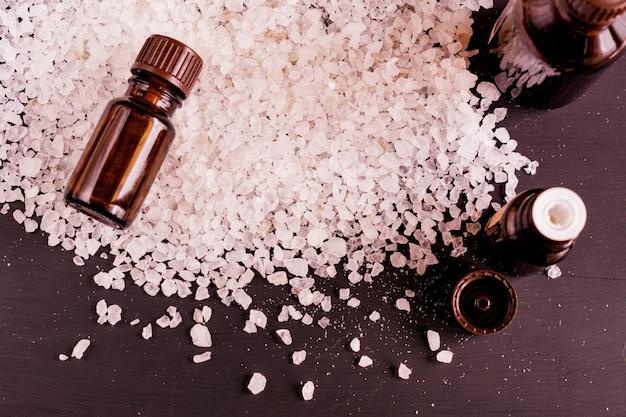 Vue de dessus des teraetments de spa - sel de mer, huiles essentielles aromatiques sur fond en bois noir
