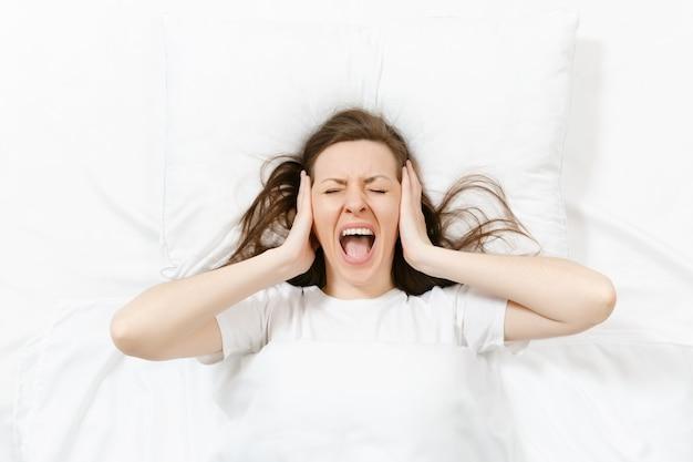 Vue de dessus de la tête d'une jeune femme brune fatiguée allongée dans son lit avec un drap blanc, un oreiller, une couverture. les femmes choquées couvrent les oreilles avec la main, passant du temps dans la chambre