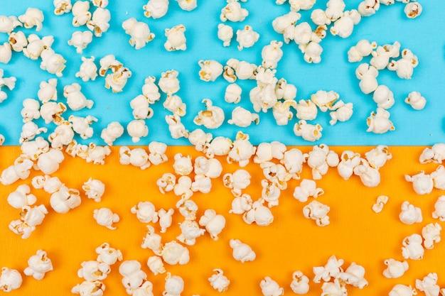 Vue de dessus de la texture du pop-corn sur horizontal bleu et jaune