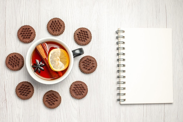 Vue de dessus thé cannelle citron arrondi avec des biscuits et un cahier sur la table en bois blanc