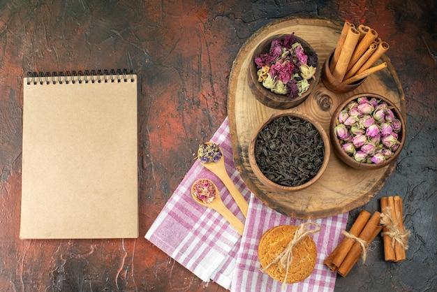 Vue de dessus thé noir frais avec des biscuits et des fleurs sur fond sombre boisson saveur thé photo café couleur fleur