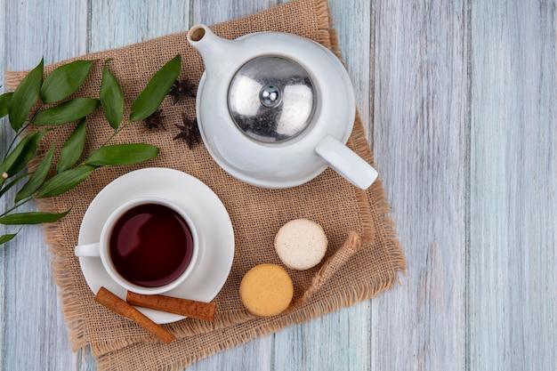 Vue de dessus théière avec une tasse de thé à la cannelle et macarons sur une serviette beige sur une table grise