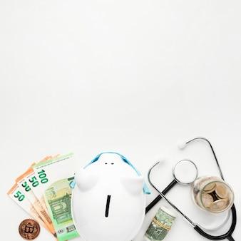 Vue de dessus tirelire avec argent et stéthoscope