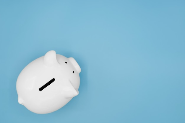 Vue de dessus de la tirelire blanche pour économiser de l'argent isolé sur fond bleu clair