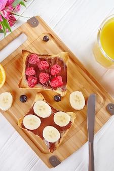 Vue de dessus sur des toasts avec du beurre d'arachide, des framboises et des bananes