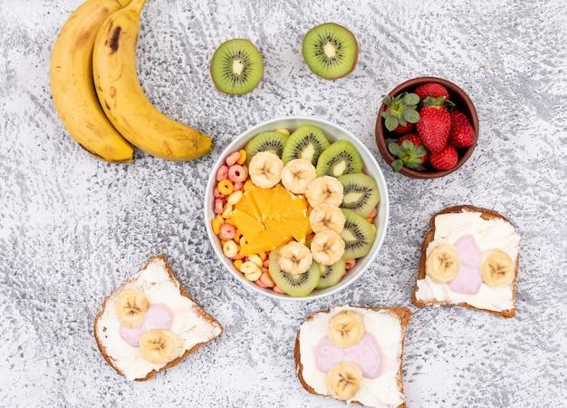 Vue de dessus des toasts avec du yaourt et des fruits sur une surface blanche horizontale