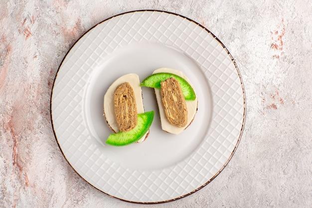 Vue de dessus des toasts de pain avec des tranches de pâté et de concombre à l'intérieur de la plaque sur le mur blanc viande légume repas sandwich toast