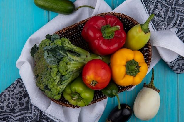Vue de dessus tomate au concombre et poivrons au brocoli dans un panier sur une serviette de cuisine sur fond turquoise