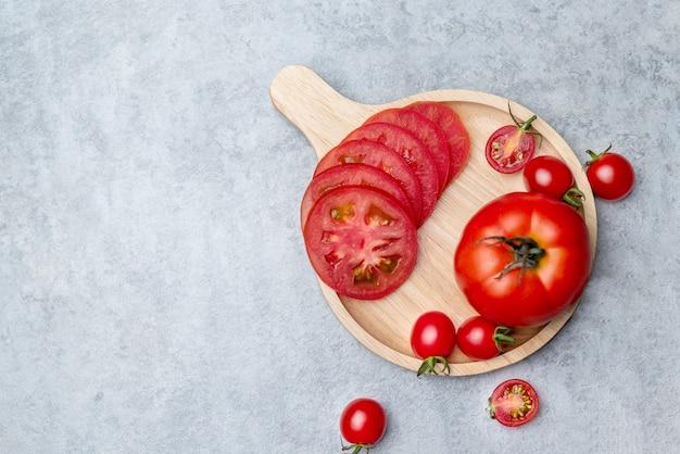 Vue de dessus de la tomate rouge en tranches, posée sur le plat en bois et placée sur une table en marbre.