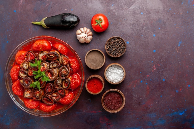 Vue de dessus tomates et aubergines repas de légumes cuits avec assaisonnements sur la surface sombre