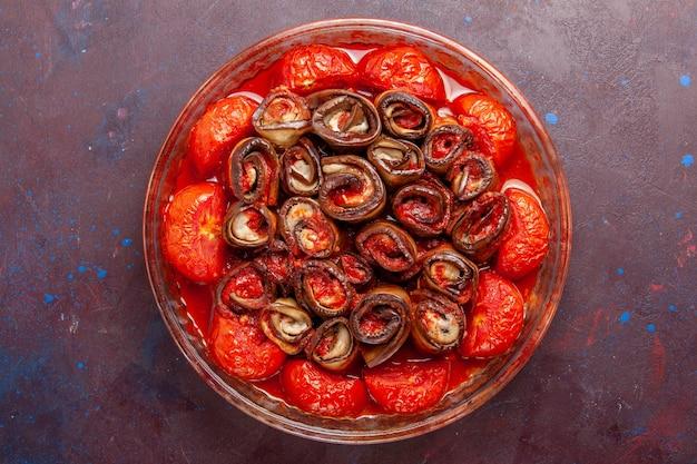 Vue de dessus tomates et aubergines repas de légumes cuits sur la surface sombre