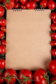 Vue de dessus des tomates autour du bloc-notes sur fond noir avec espace de copie