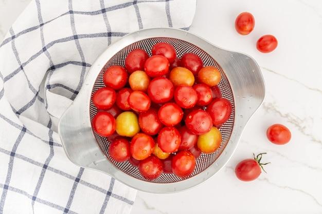 Vue de dessus des tomates cerises fraîches dans une passoire prête à être cuite