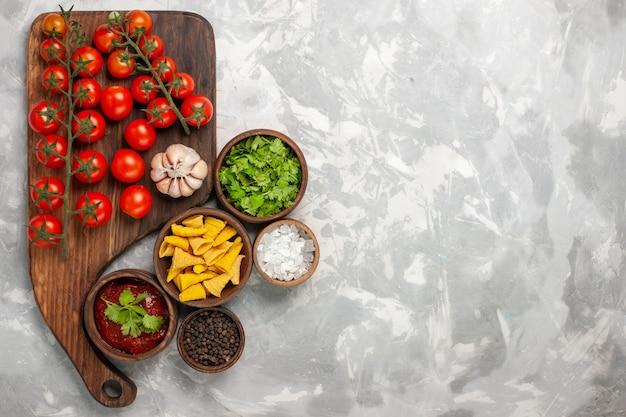 Vue de dessus tomates cerises fraîches avec différents assaisonnements et légumes verts sur une surface blanche