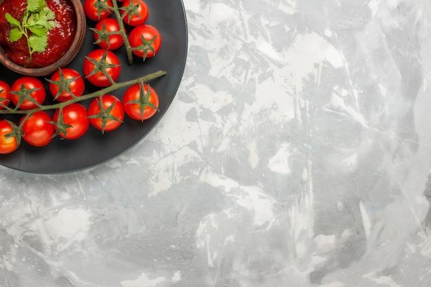 Vue de dessus tomates cerises fraîches à l'intérieur de la plaque sur la surface blanche