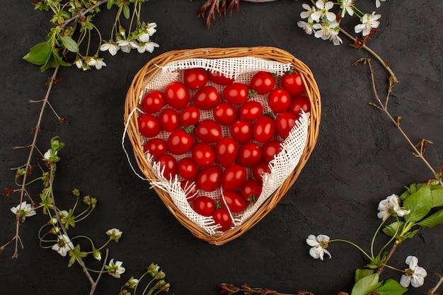 Vue de dessus des tomates cerises rouges fraîches à l'intérieur du panier sur le fond sombre