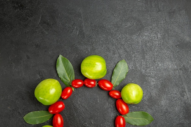 Vue de dessus tomates cerises tomates vertes et feuilles de laurier sur le fond du sol sombre avec de l'espace libre