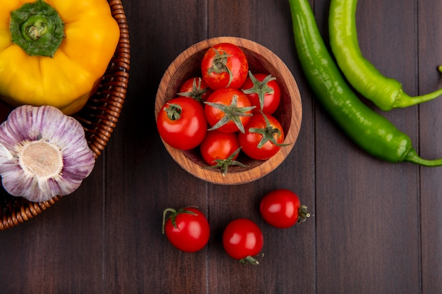 Vue de dessus des tomates dans un bol et de l'ail poivré dans le panier sur la surface en bois