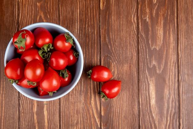 Vue de dessus des tomates dans un bol avec d'autres sur le côté gauche et bois avec espace copie