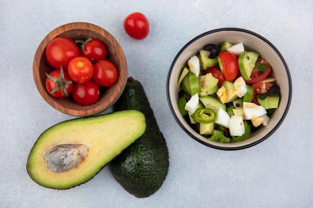 Vue de dessus des tomates dans un bol en bois avec avocat près de salade de légumes dans un bol sur une surface blanche
