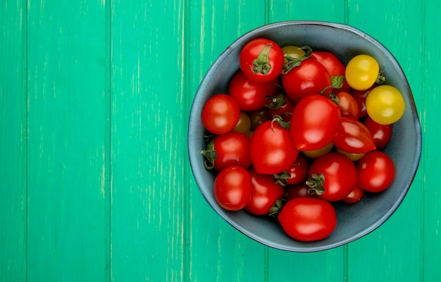 Vue de dessus des tomates dans un bol sur le côté droit et la surface verte avec copie espace