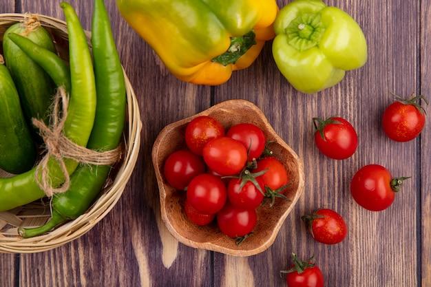 Vue de dessus des tomates dans un bol et des poivrons dans le panier et sur la surface en bois