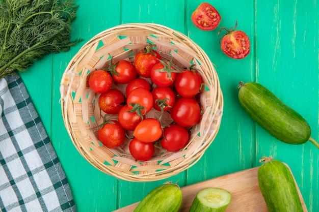 Vue de dessus des tomates dans le panier et de l'aneth de concombre autour sur la surface verte