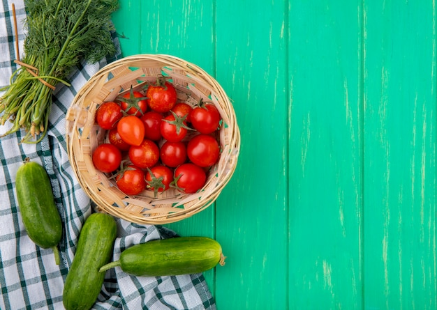 Vue de dessus des tomates dans le panier et de l'aneth de concombre autour de tissu à carreaux et surface verte