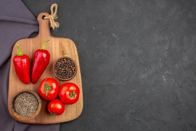 Vue de dessus des tomates fraîches avec assaisonnements sur fond noir