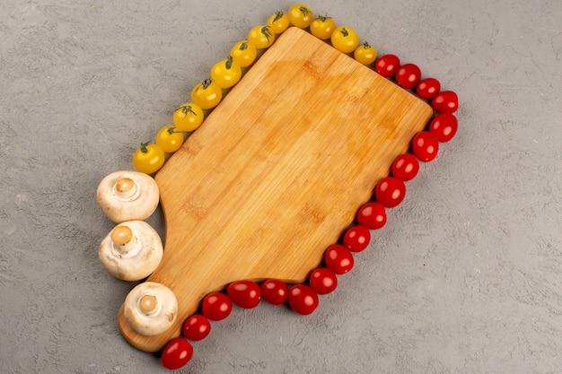 Vue de dessus de tomates fraîches tomates mûres fraîches jaunes et rouges bordées de champignons sur le bureau gris