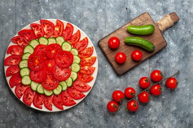 Vue de dessus des tomates fraîches en tranches élégamment conçues avec des concombres sur un espace rustique gris