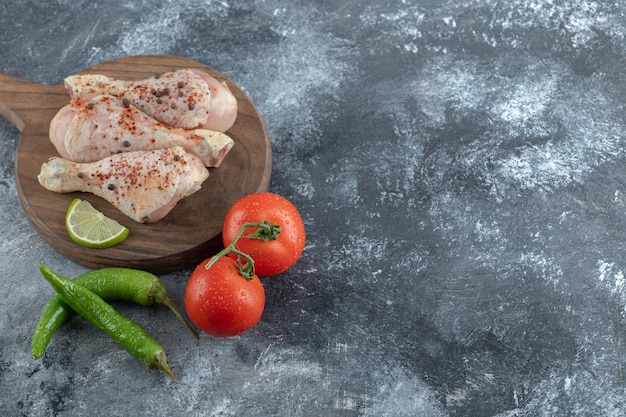 Vue de dessus. tomates et poivrons biologiques frais avec cuisses de poulet crues