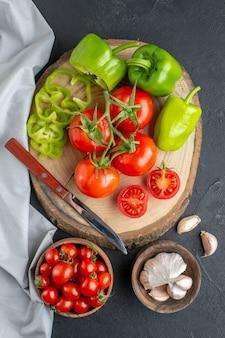 Vue de dessus tomates rouges fraîches à l'ail et poivrons verts sur une surface sombre