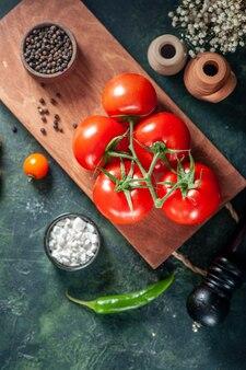 Vue de dessus tomates rouges fraîches sur la surface sombre légume salade mûre fraîche repas alimentaire couleur poivre